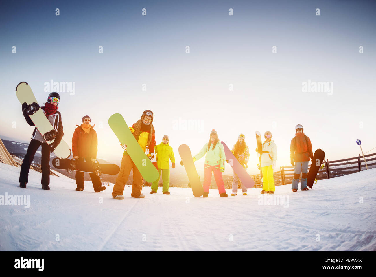 Happy friends snowboarders are having fun at ski resort against sunset light - Stock Image