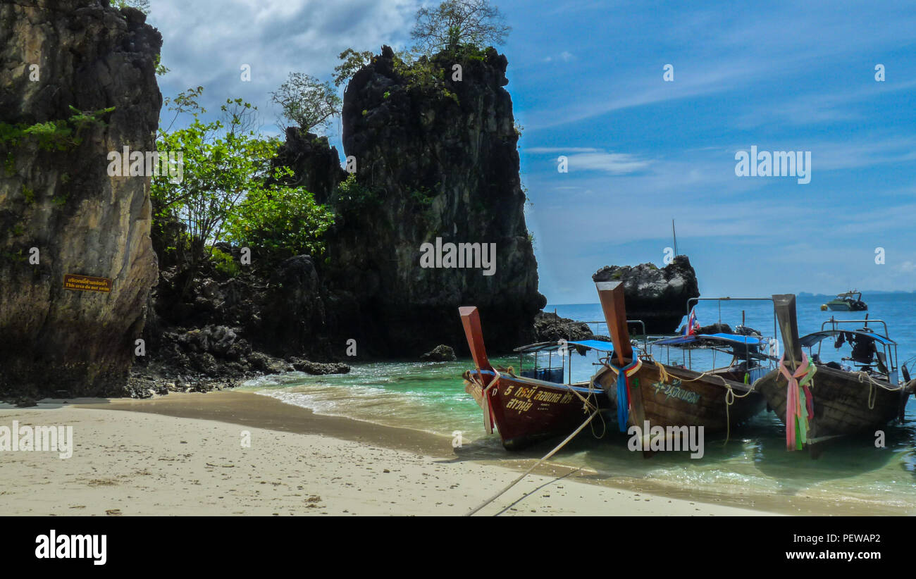 Landscape view of three long-tail boats waiting of one of the beaches of Krabi in Thailand, with limestones cliffs on the left - Stock Image