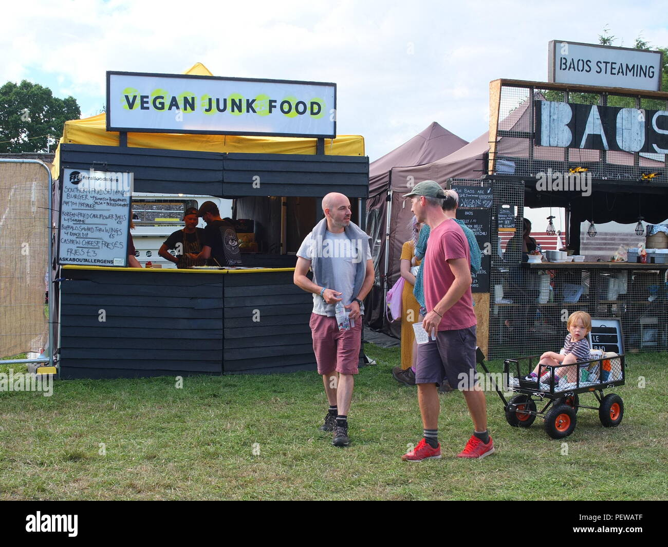 'Vegan Junk Food' stall at Green Man Festival, Wales, two men with child in cart in front of stall, vegan fast food - Stock Image