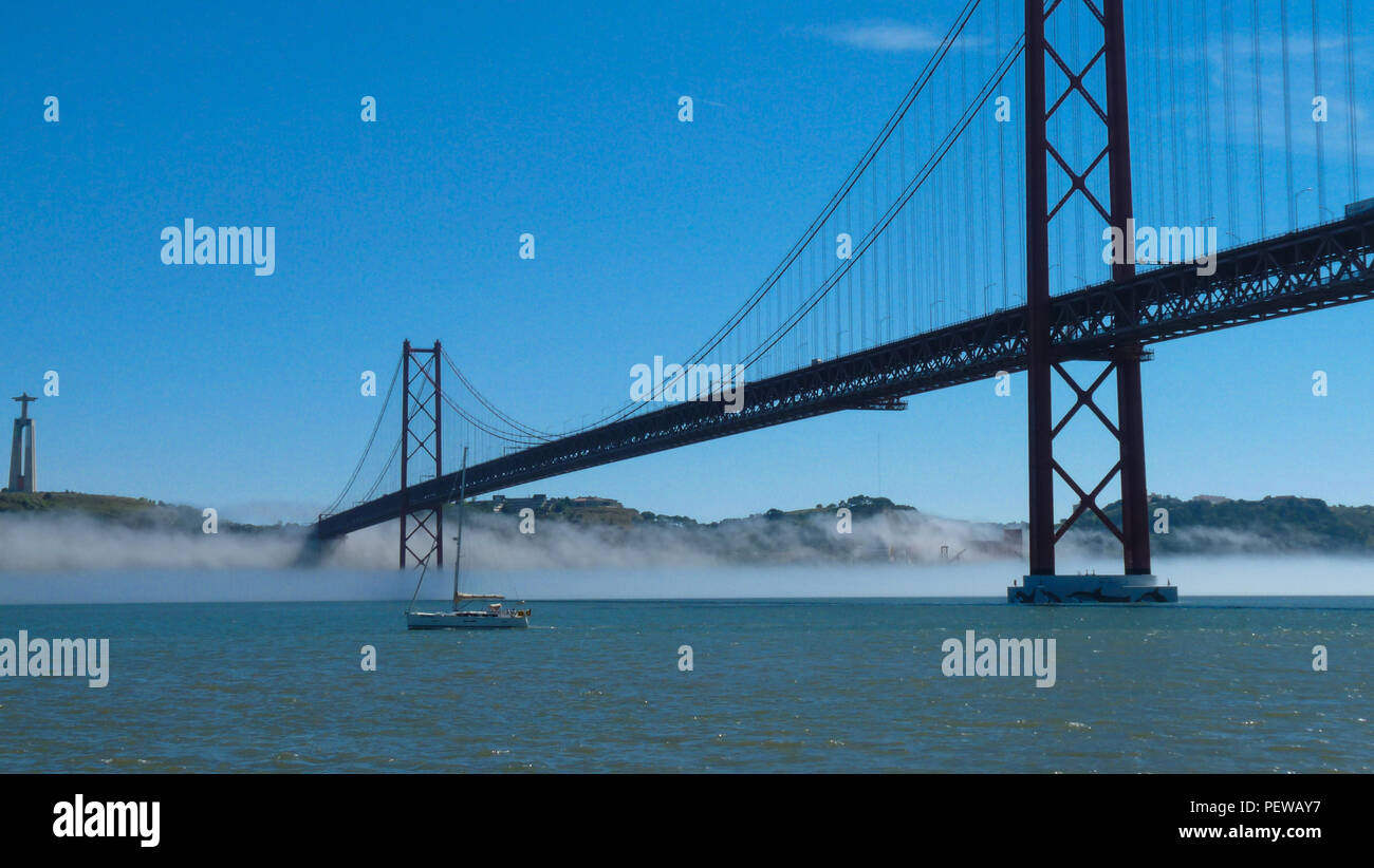 Landscape view of the 25 de Abril Bridge in Lisbon, Portugal, with a small mist underneath it an a boat passing on the Tagus River Stock Photo