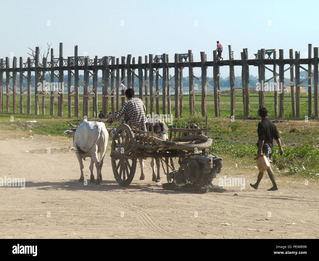 Landscape view of the U Bein Bridge in Amarapura, Myanmar, with locals on an old Ox cart in the foreground - Stock Image