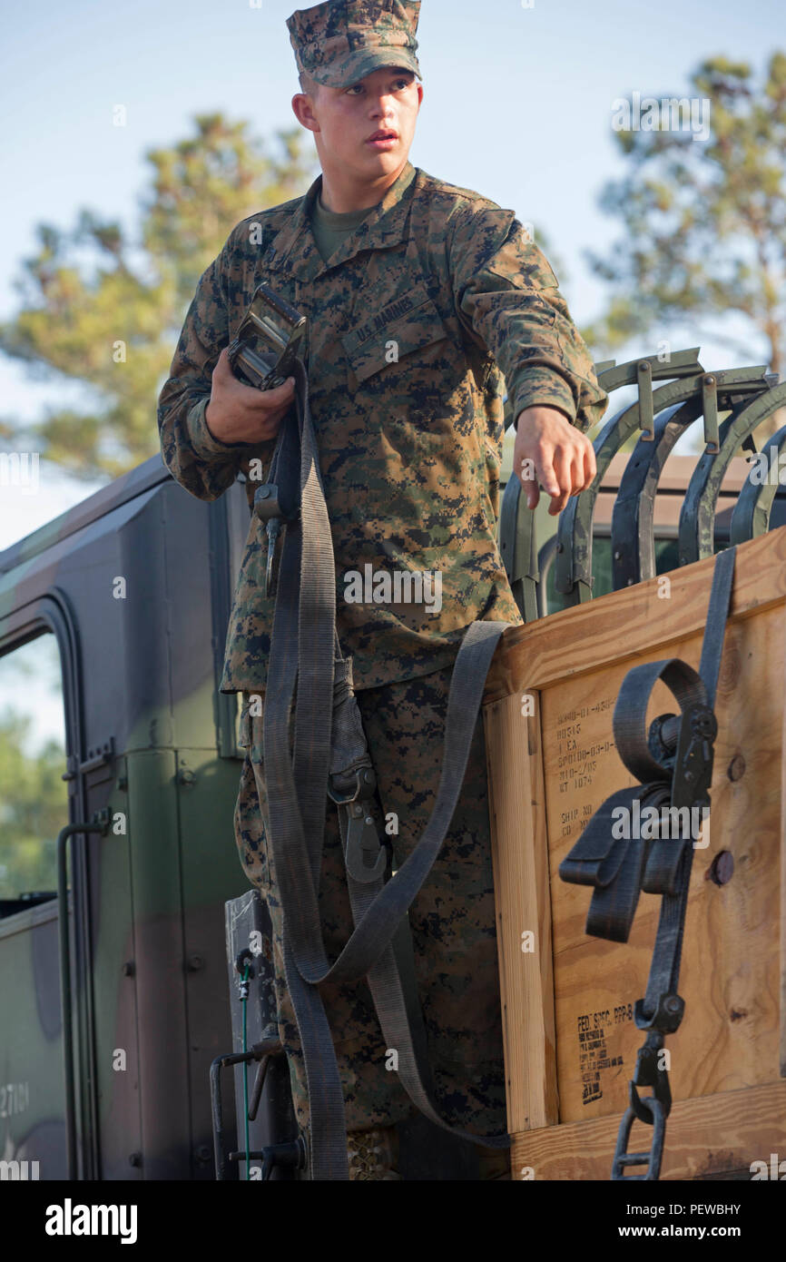 U.S. Marine Corps Lance Cpl. Richard K. Steiner, Service Company, Headquarters Regiment, 2nd Marine Logistics Group secures pieces of gear to a 7-ton Medium Tactical Vehicle Replacement following a Command Post Exercise (CPX) at Landing Zone Robin on Camp Lejeune, N.C., Feb. 3, 2016. Marines participated in the CPX in order to maintain operational readiness. (U.S. Marine Corps photo by Lance Cpl. Tyler W. Stewart/Released) - Stock Image