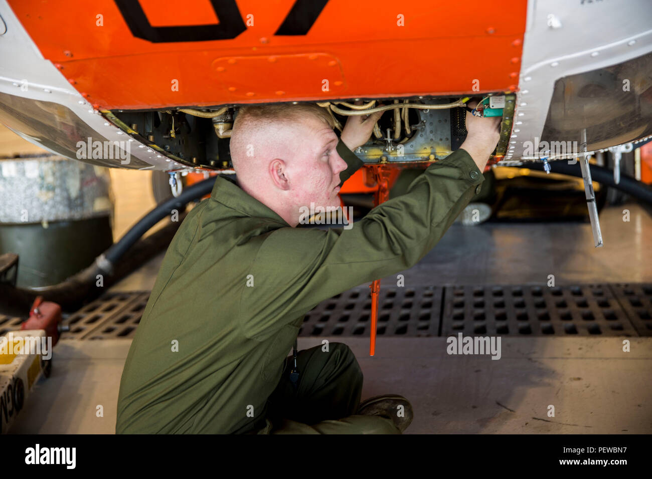 """Lance Cpl. Kalib Turner, a corrosion treatment avionics technician chief with Headquarters and Headquarters Squadron Search and Rescue (SAR), stationed out of Marine Corps Air Station Yuma, Ariz., checks for corrosion in the circuit breaker box of a HH-1N """"Huey"""" helicopter in the SAR hangar, Thursday, Feb. 4, 2016. - Stock Image"""