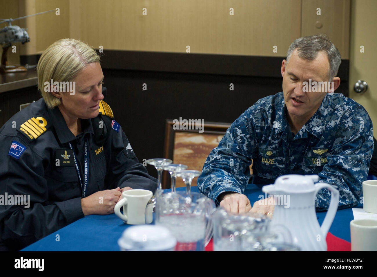 160204-N-VR008-066 SAN DIEGO (Feb. 4, 2016) – Capt. Michael W. Baze, commanding officer of the amphibious assault ship USS America (LHA 6), discusses operations with New Zealand Royal Navy Capt. Lisa Hunn during a tour of the ship. America is currently undergoing a post-shakedown availability (PSA) in which the ship's crew and assigned contractors make improvements to the ship's design. (U.S. Navy photo by Mass Communication Specialist 3rd Class Kyle Goldberg/Released) - Stock Image