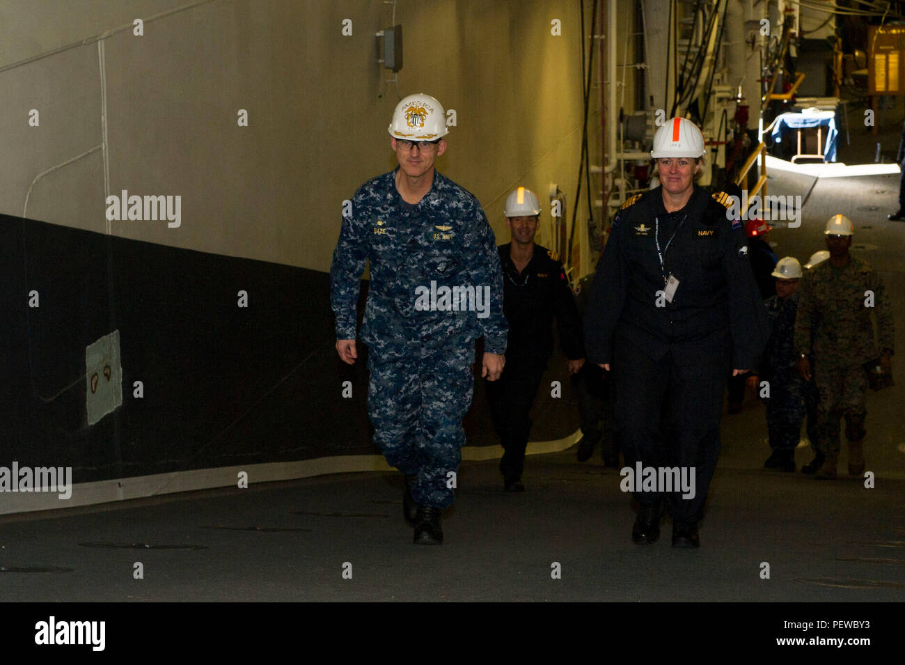 160204-N-VR008-054 SAN DIEGO (Feb. 4, 2016) – Capt. Michael W. Baze, commanding officer of the amphibious assault ship USS America (LHA 6), guides New Zealand Royal Navy officers during a tour of the ship. America is currently undergoing a post-shakedown availability (PSA) in which the ship's crew and assigned contractors make improvements to the ship's design. (U.S. Navy photo by Mass Communication Specialist 3rd Class Kyle Goldberg/Released) - Stock Image