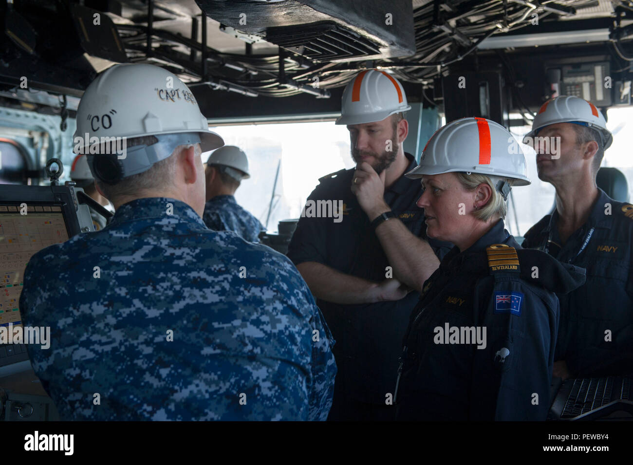160204-N-VR008-051 SAN DIEGO (Feb. 4, 2016) – Capt. Michael W. Baze, commanding officer of the amphibious assault ship USS America (LHA 6), gives New Zealand Royal Navy officers a tour of the ship's bridge. America is currently undergoing a post-shakedown availability (PSA) in which the ship's crew and assigned contractors make improvements to the ship's design. (U.S. Navy photo by Mass Communication Specialist 3rd Class Kyle Goldberg/Released) - Stock Image