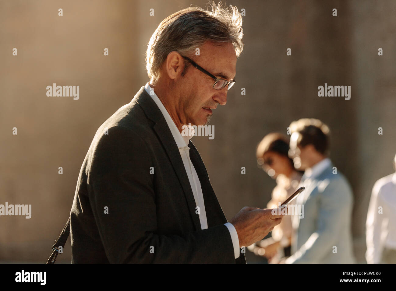 Man in formal clothes looking at his mobile phone while commuting to office. Busy office going person walking on street and using his mobile phone. - Stock Image