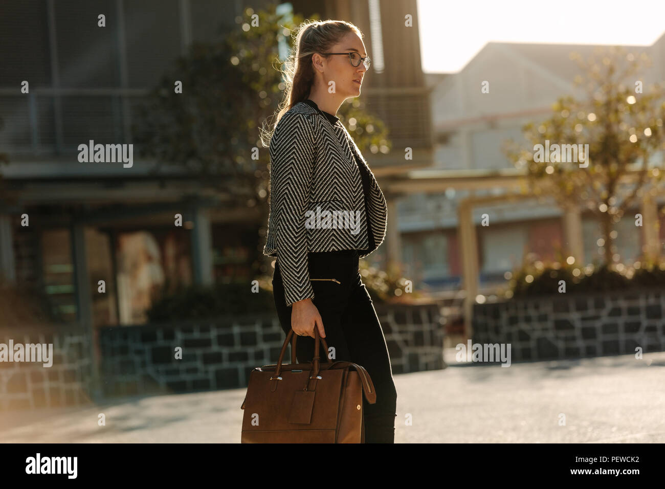 Woman walking on a street in the morning. Businesswoman commuting to office in the morning carrying her bag. - Stock Image