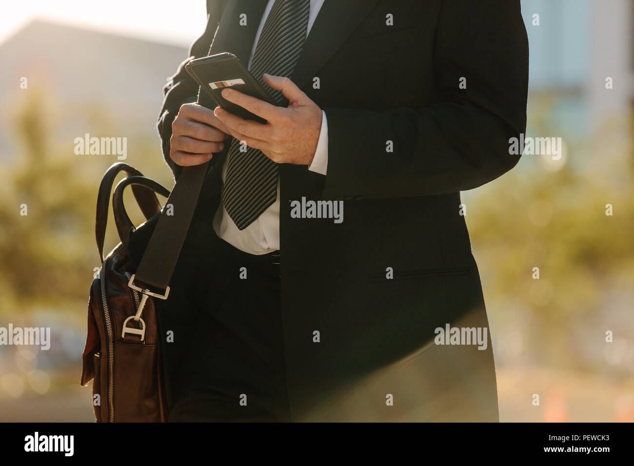 Mid section of a man in formal clothes using his mobile phone while commuting to office. Busy office going man walking on street and using his mobile  - Stock Image