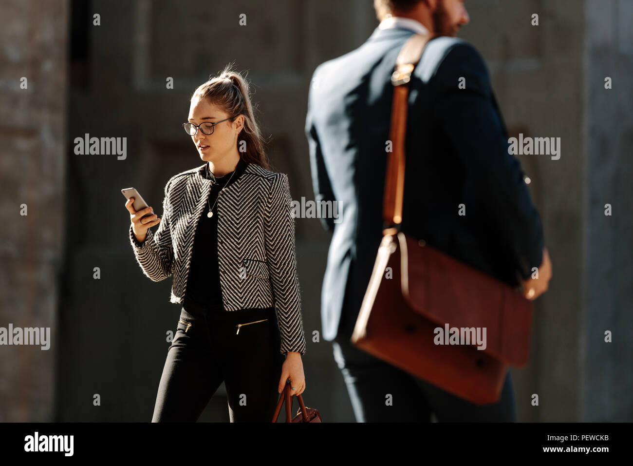 Businesswoman commuting to office in the morning looking at her mobile phone. Business people walking on city street to office carrying their office b - Stock Image