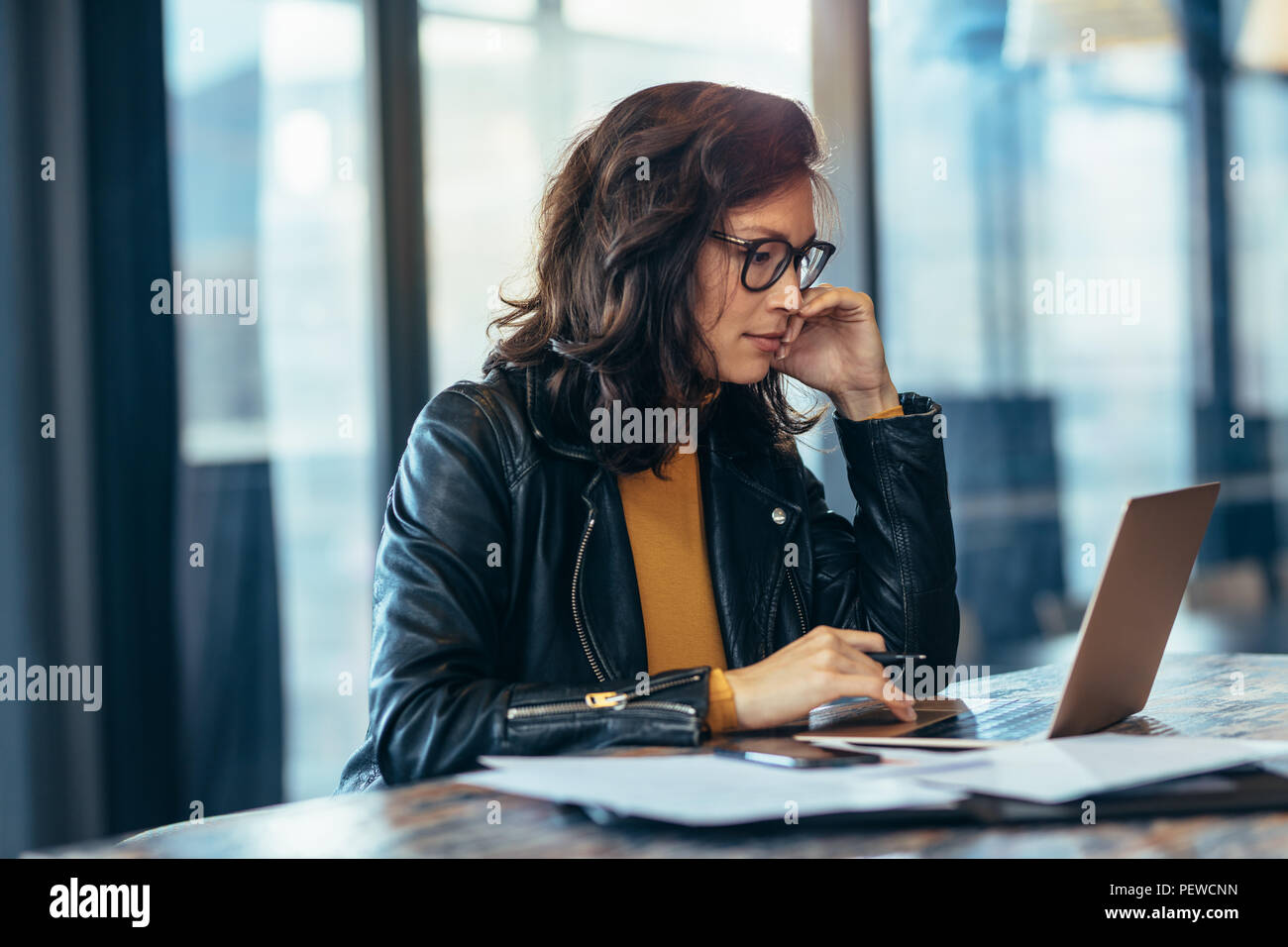 Portrait of woman working on laptop computer in office. Asian business woman in casuals working at office. - Stock Image