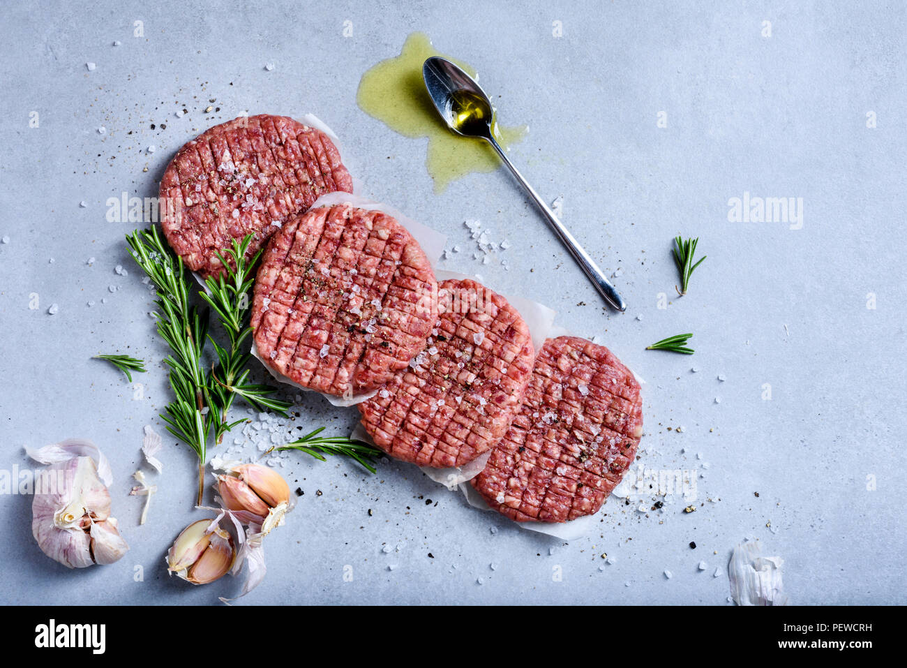 Homemade raw minced beef steak burgers with spices and herbs, organic healthy food cooking, top view, flat lay. - Stock Image