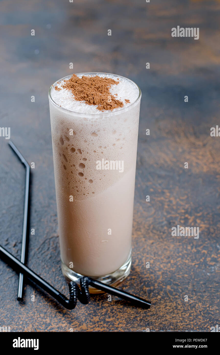 Milk chocolate cocktail or cold whipped coffee with milk and ice sprinkle cocoa on dark background, copy space, - Stock Image