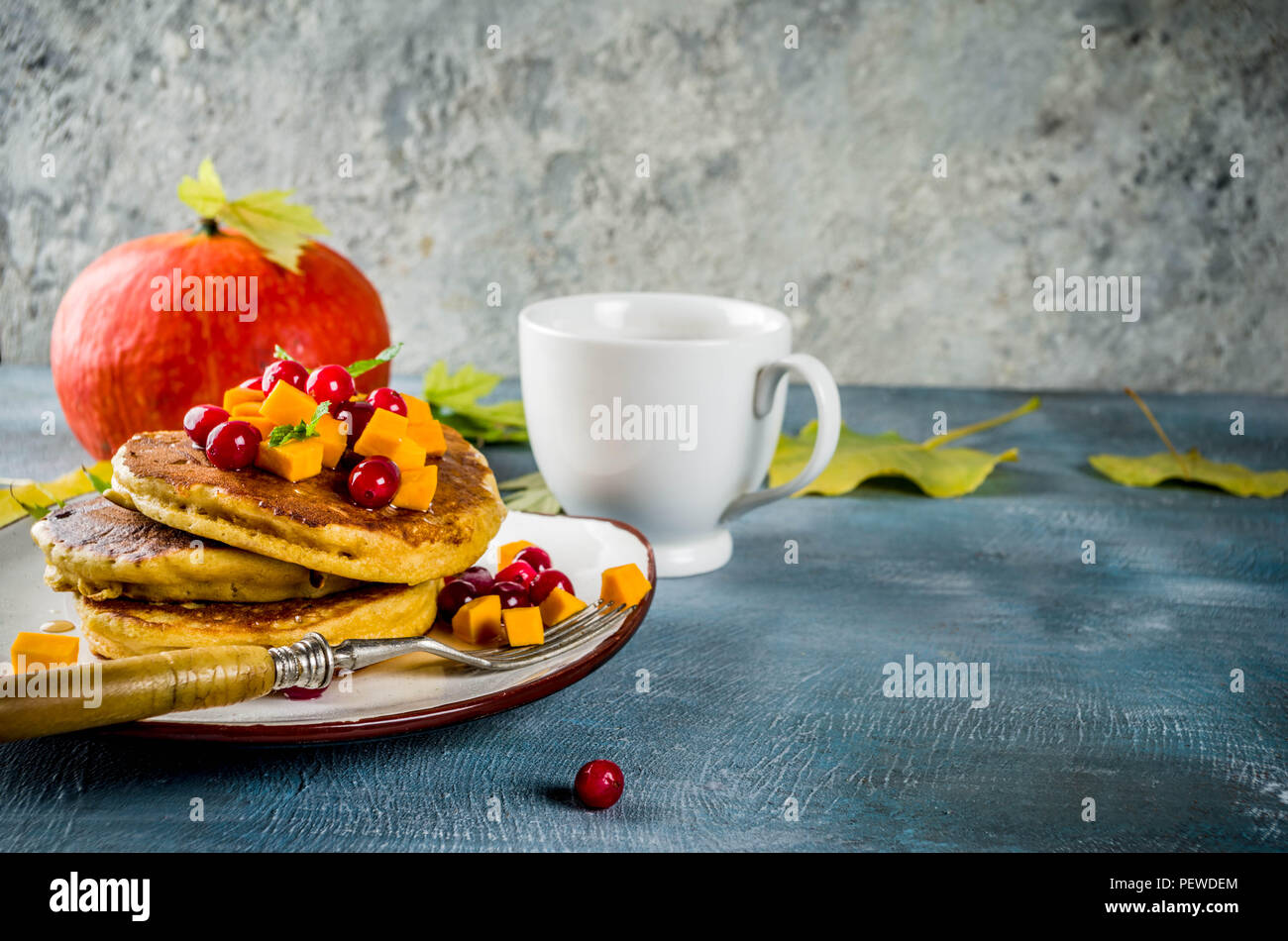 Autumnal breakfast idea, pumpkin pancakes, with slices of pumpkin, maple syrup or honey, cranberry, on a blue concrete background, space for text Stock Photo