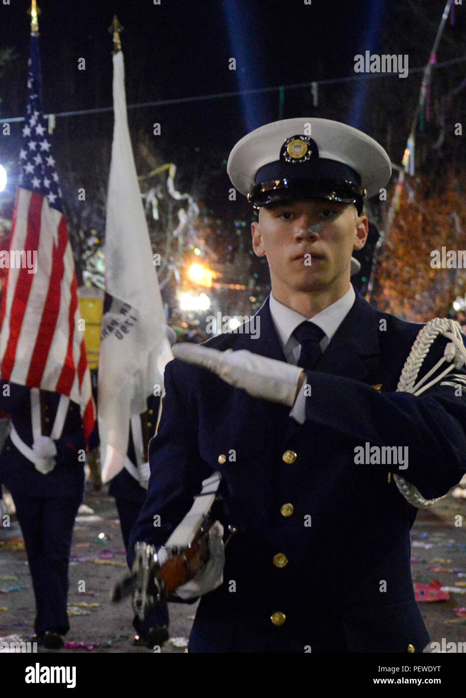 A member of the Coast Guard Ceremonial Honor Guard marches down the streets of New Orleans during the 2016 Bacchuc Mardi Gras Parade while performing a rifle routine, Feb. 7, 2016. Members of the Coast Guard Ceremonial Honor Guard perform silent drills around the country as representatives of the Coast Guard. (U.S. Coast Guard photo by Petty Officer 2nd Class Jonathan Lally) Stock Photo