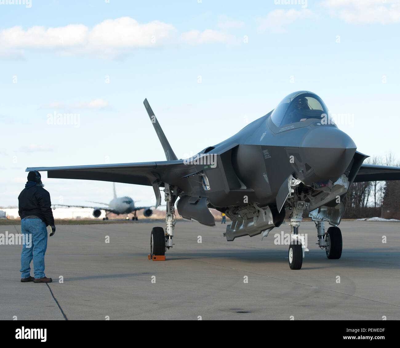 160205-O-ZZ999-924 NAS Patuxent River (February 5, 2016) A member of the Pax River Integrated Test Force (ITF) stands at the ready as Italian Air Force (Aeronautica Militare) aircraft AL-1 — the first F-35 Lightning II international jet fully built overseas at the Cameri Final Assembly & Check-Out (FACO) facility at Cameri Air Base, Italy — arrives at the Navy's Electromagnetic Environmental Effects (EEE) test and evaluation laboratory aboard Naval Air Station (NAS) Patuxent River on Feb. 5, 2016. (U.S. Navy photo courtesy Andy Wolfe/Released) - Stock Image