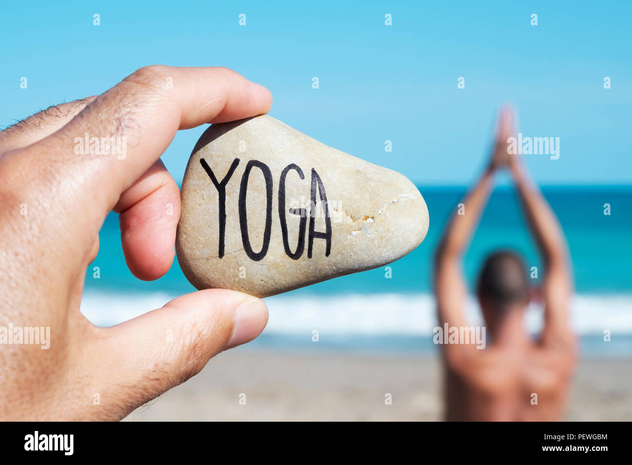 closeup of the hand of a young caucasian man on the beach holding a stone with the yoga written in it, and a young caucasian man practicing yoga in th - Stock Image