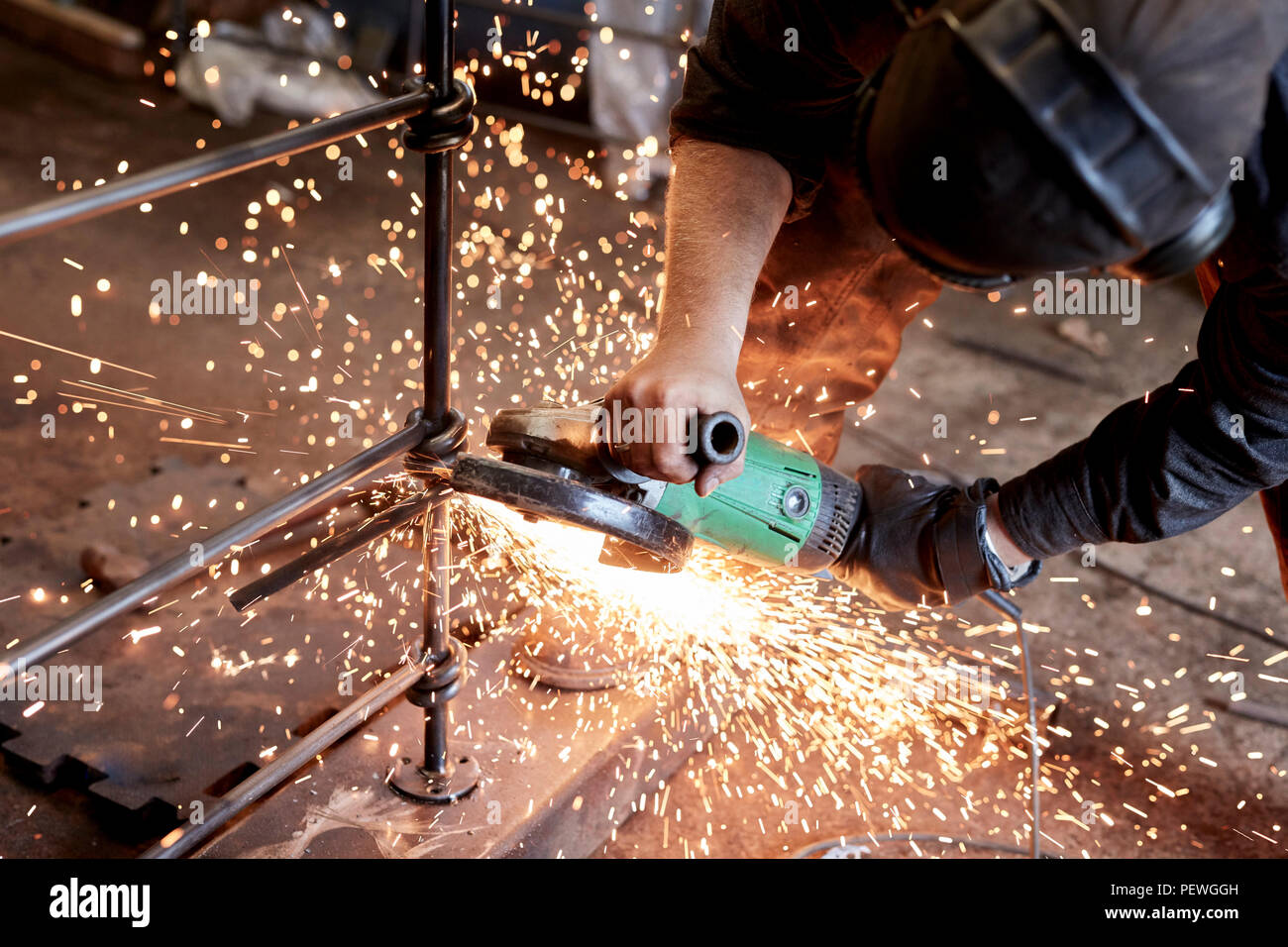 An artisan metalworker at work holding an angle grinder, workng on a metal fence. - Stock Image