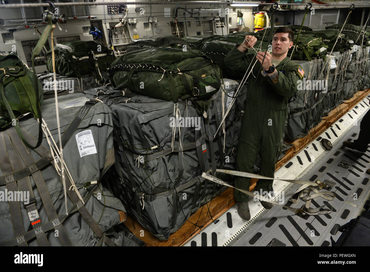 U.S. Air Force Senior Airman Glen Baker, 7th Airlift Squadron, loads a C-17 Globemaster III with container delivery systems from McChord Air Force Base, Wash., during Large Package Week at Pope Army Airfield, N.C., Feb. 4, 2016. Large Package Week leads up to Joint Operational Access Exercise 16-5, where in Army and Air Force units work together to improve interoperability for worldwide crisis, contingency and humanitarian operations. (U.S. Air Force photo by Staff Sgt. Sandra Welch) Stock Photo