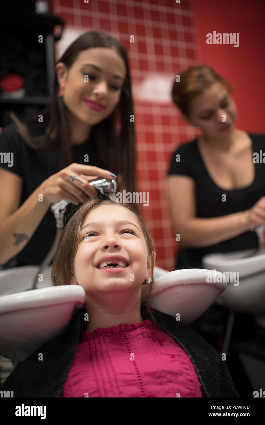 Hairdressers with little girls, washing hair in sink - Stock Image