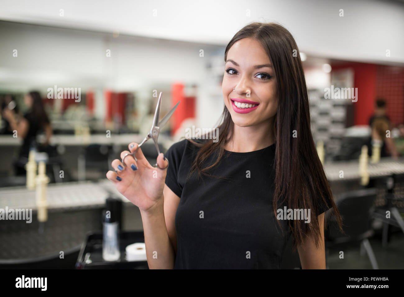 Hairdressers with scissors posing in salon smiling looking at camera - Stock Image