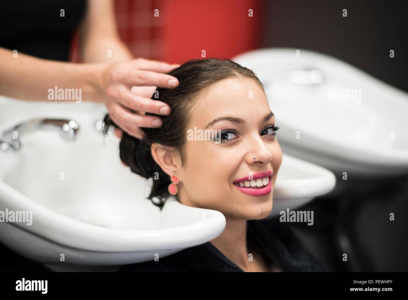 Hairdresser washing latin woman hair in hairdressing saloon sink - Stock Image