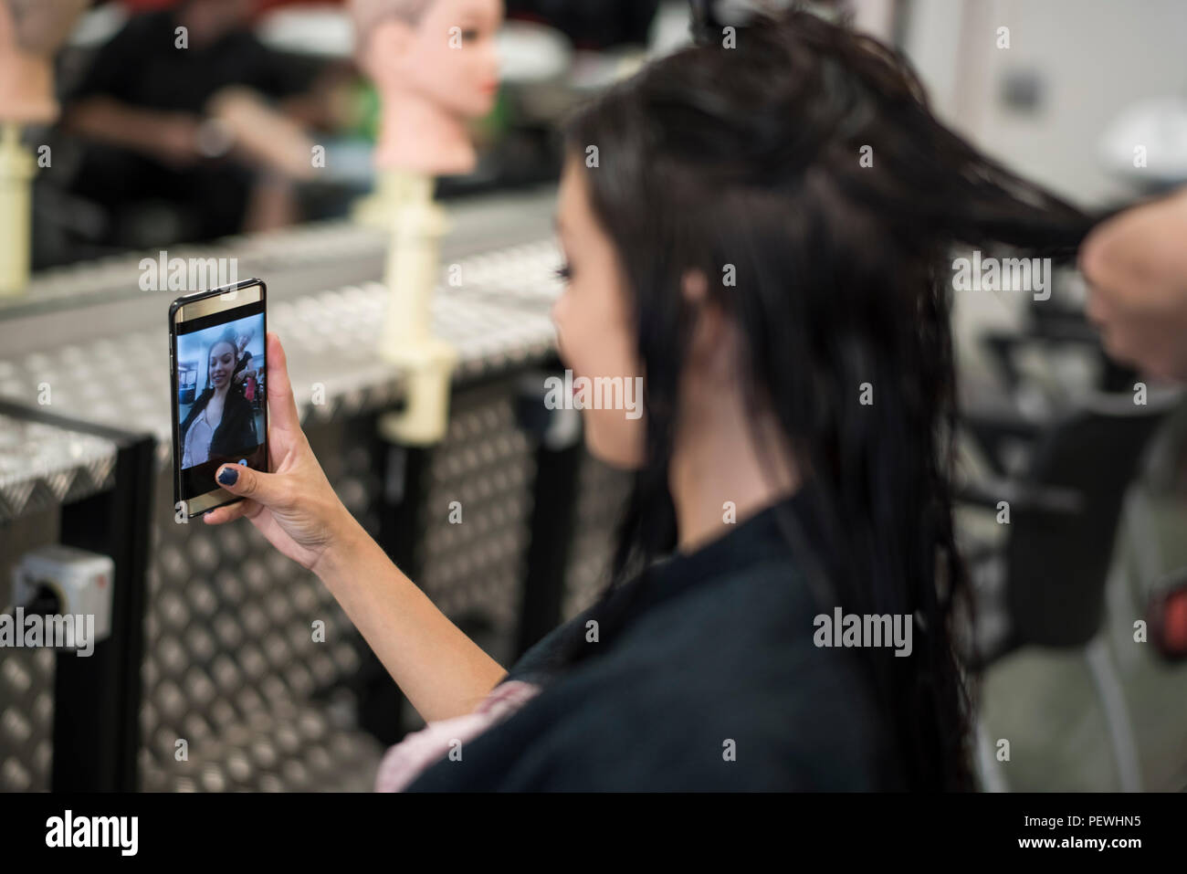 Hairdresser cuts and comb young womans hair - Stock Image