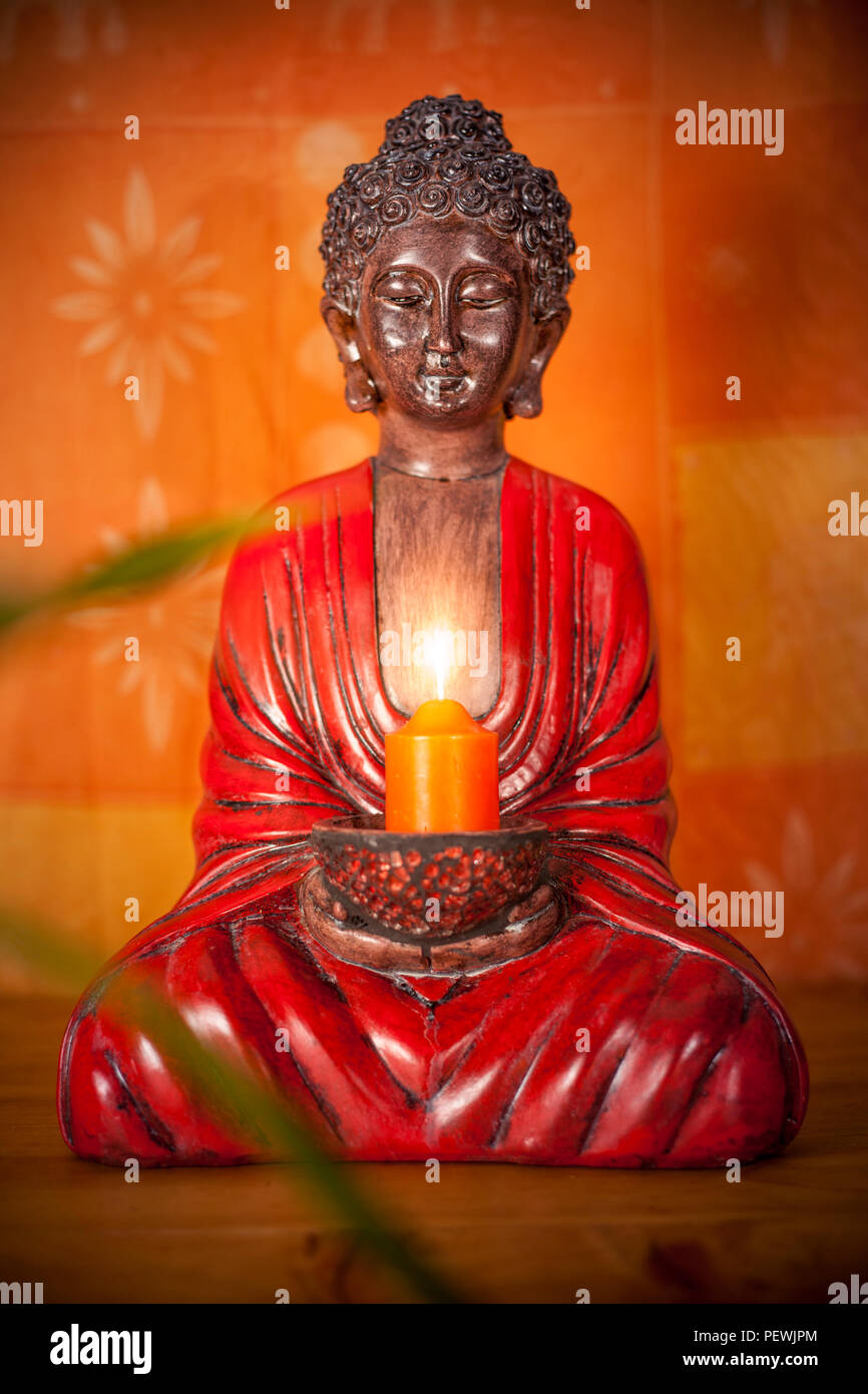 Buddha Zen Statue Holding A Candle With Warm Orange Light And Bamboo Leafs Stock Photo Alamy