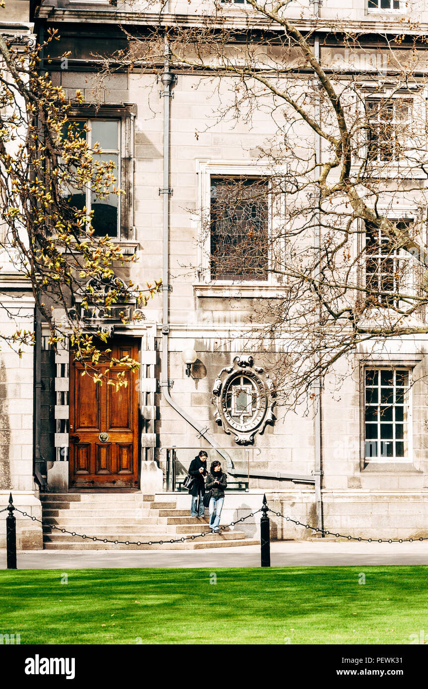 Dublin, Ireland - April 4, 2010: Two young women stand on the steps of an old building on campus of the Trinity College Dublin. - Stock Image