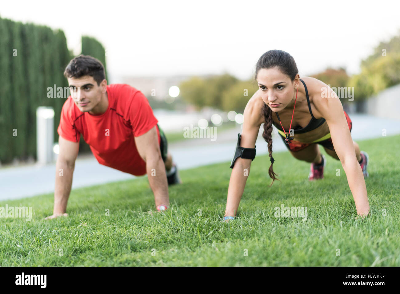 Coupe training push ups exercises in city park at night - Stock Image