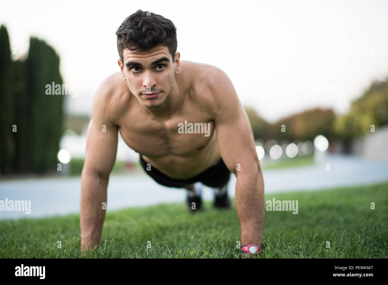 Man training fitness and running in public city park - Stock Image