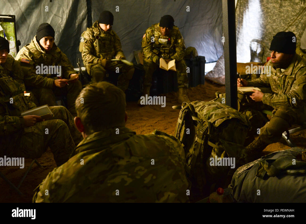 Sgt. Warren Bridenthal (front left and facing the Soldiers), a forward observer with 3rd Squadron, 2nd Cavalry Regiment, stationed out of Vilseck, Germany, originally from Riverside, Calif., refreshes the Reconnaissance Platoon on how to 'call for fire' during a night training exercise at Adazi Training Area in Latvia, Feb. 3, 2016. (Photo by U.S. Army Staff Sgt. Steven M. Colvin/Released) - Stock Image