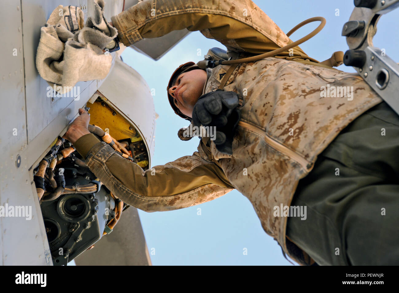 U.S. Marine Lance Cpl. Edgar Santibanez, Marine Medium Tiltrotor Squadron 363, 3rd Marine Aircraft Wing, wipes down the propulsion engine of an MV-22 Osprey during Integrated Training Exercise 2-16 at Marine Corps Air Ground Combat Center, Twentynine Palms, Calif., Jan. 25, 2016. MCAGCC conducts relevant live-fire combined arms, urban operations, and joint/coalition level integration training that promote operational forces' readiness. (U.S. Air Force photo by Tech. Sgt. Joselito Aribuabo/Released) - Stock Image