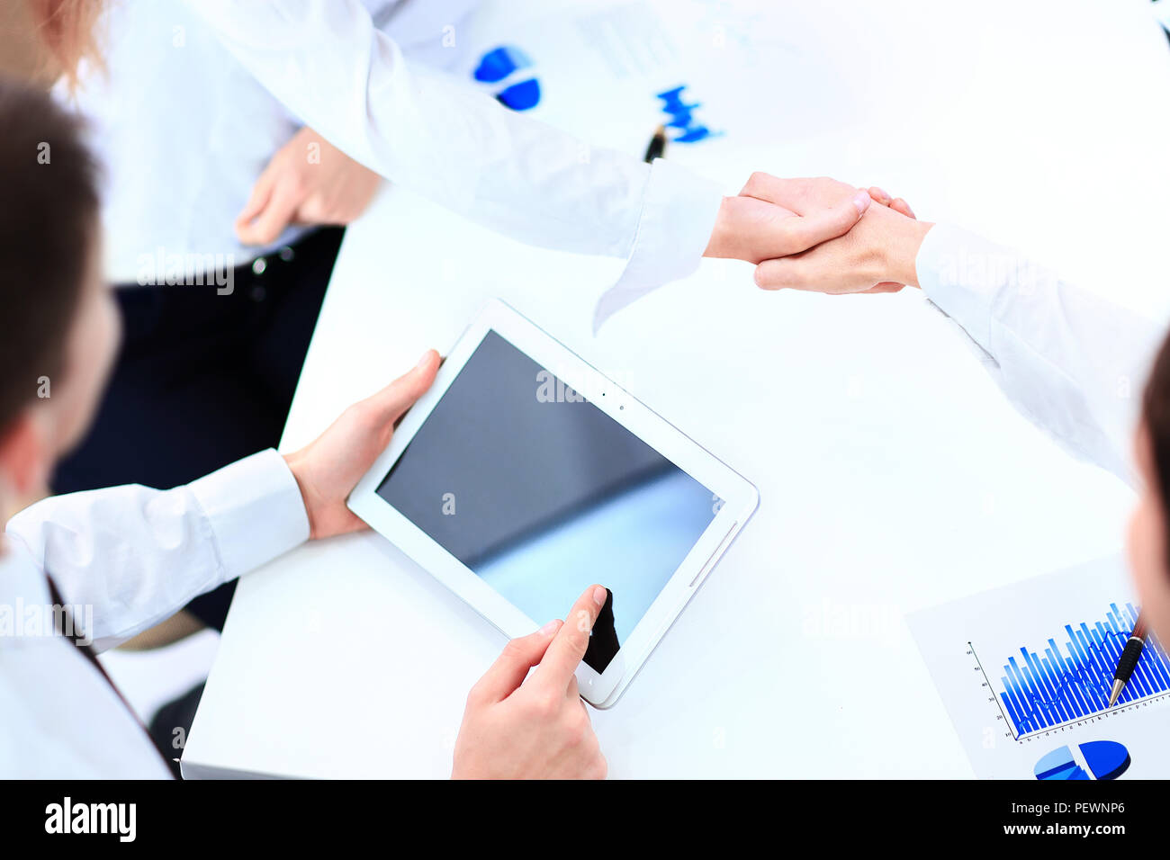 Image of human hand pointing at touchscreen with business document - Stock Image