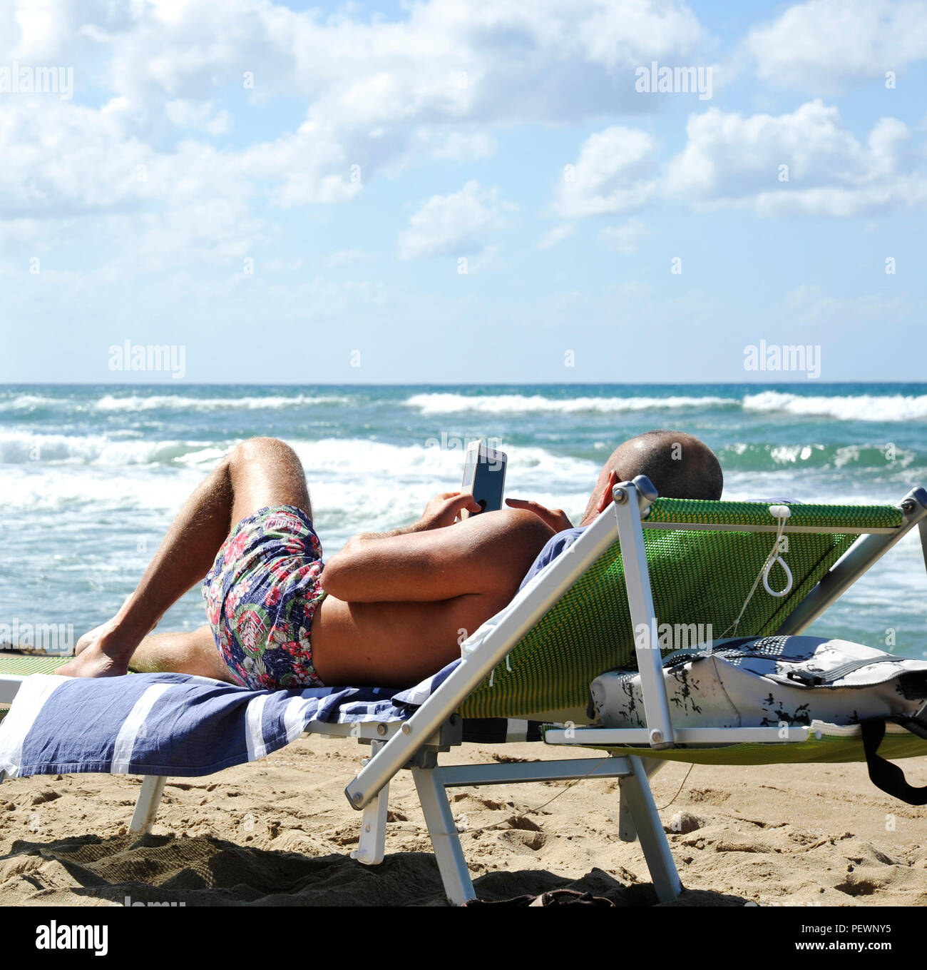 Man at the beach lying on the sunbed looking at the smartphone. In the background two men contemplate the sea. There is contemplation and contemplatio - Stock Image