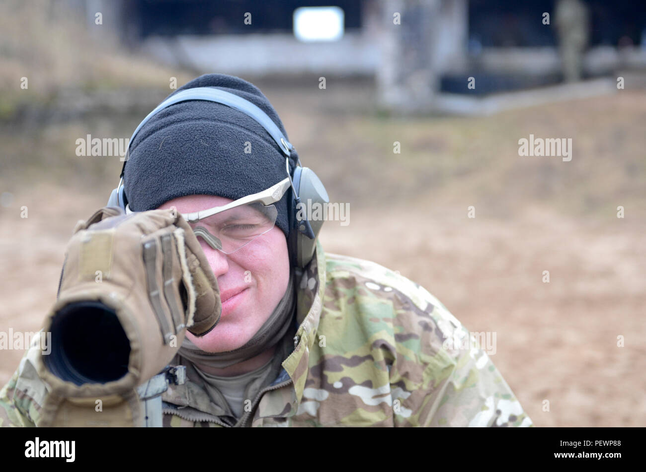 Sgt. John Zagozdon, a sniper with 3rd Squadron, 2nd Cavalry Regiment, stationed out of Vilseck, Germany, originally from Chicago, looks through monoculars to identify whether or not the enemy target was hit during a field training exercise at Adazi Training Area in Latvia, Feb. 3, 2016. (Photo by U.S. Army Staff Sgt. Steven M. Colvin/Released) - Stock Image