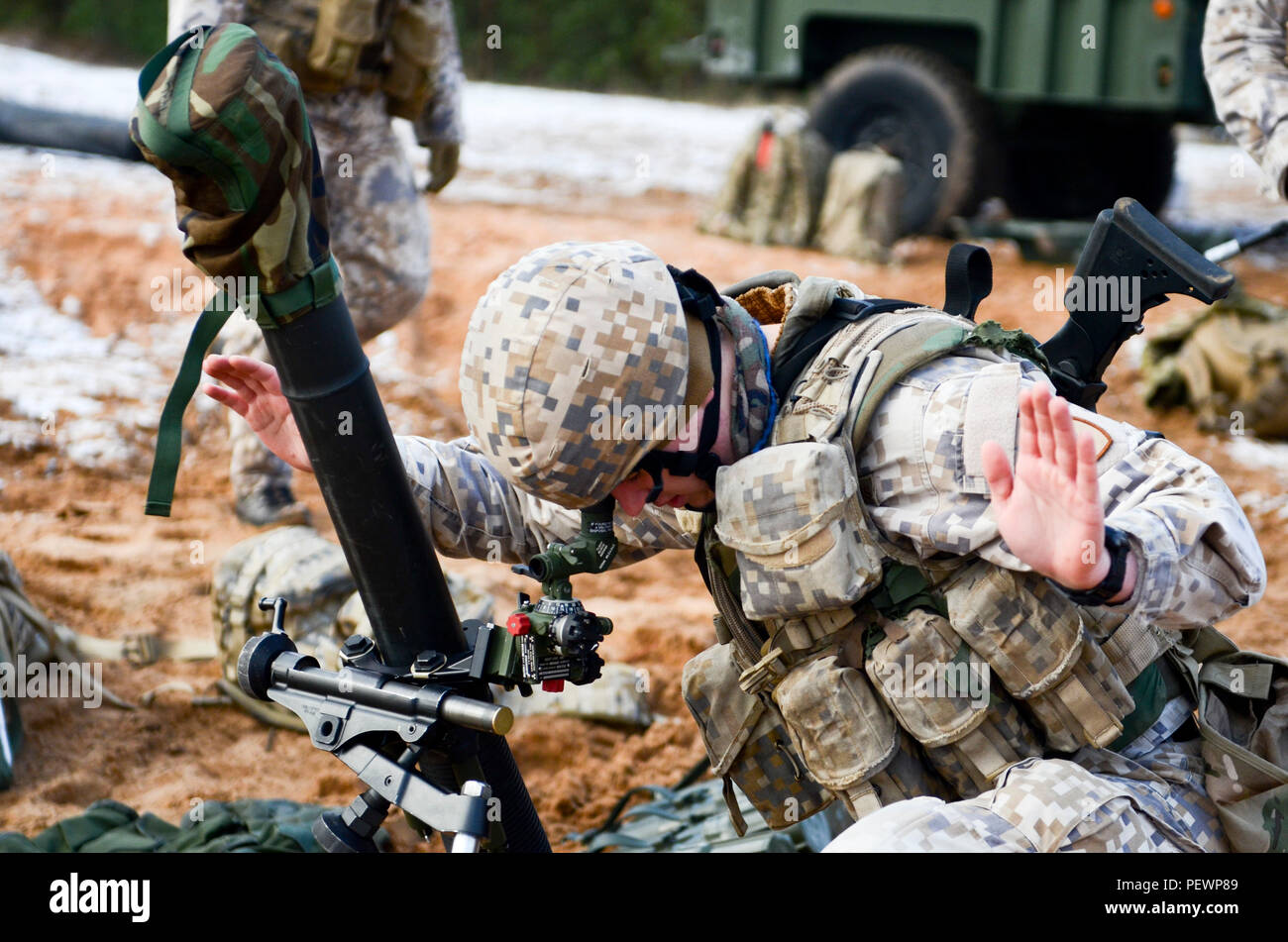 A Latvian soldier with the Latvian Mortar Corps gives hand signals to a fellow soldier in order to align the aiming poles with the sight unit during a field training exercise, which Soldiers of 3rd Squadron, 2nd Cavalry Regiment, stationed out of Vilseck, Germany, participated in at Adazi Training Area in Latvia, Feb. 4, 2016. (Photo by U.S. Army Staff Sgt. Steven M. Colvin/Released) - Stock Image