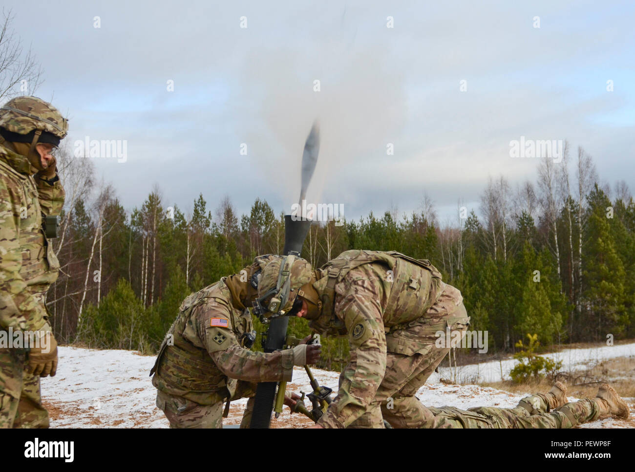 An 81 mm mortar round can be seen as Soldiers of 3rd Squadron, 2nd Cavalry Regiment, stationed out of Vilseck, Germany, shoot it out of an M252 Mortar System during a joint training exercise in Adazi Training Area in Latvia, Feb. 4, 2016. (Photo by U.S. Army Staff Sgt. Steven M. Colvin/Released) - Stock Image