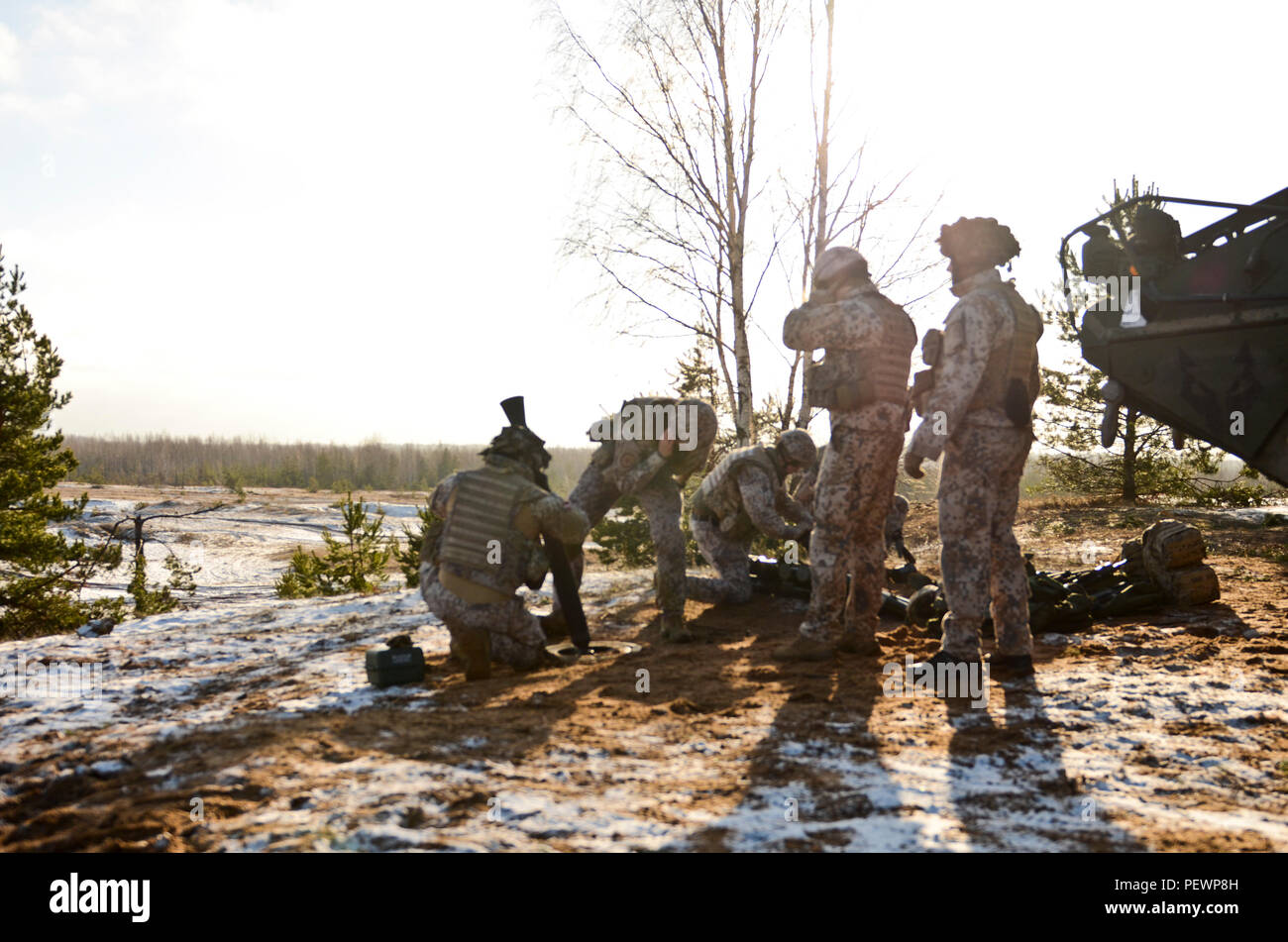 As the sun shines through the clouds, the Latvian mortar soldiers prepare themselves for the firing of an 81 mm mortar round during a joint field training exercise at Adazi Training Area in Latvia, Feb. 4, 2016. (Photo by U.S. Army Staff Sgt. Steven M. Colvin/Released) - Stock Image