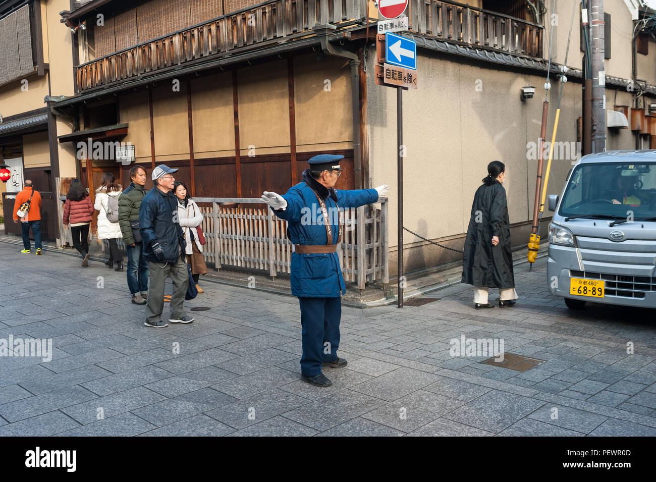 23.12.2017, Kyoto, Japan, Asia - A traffic warden is seen regulating the flow of traffic at an intersection in Kyoto's old city. - Stock Image