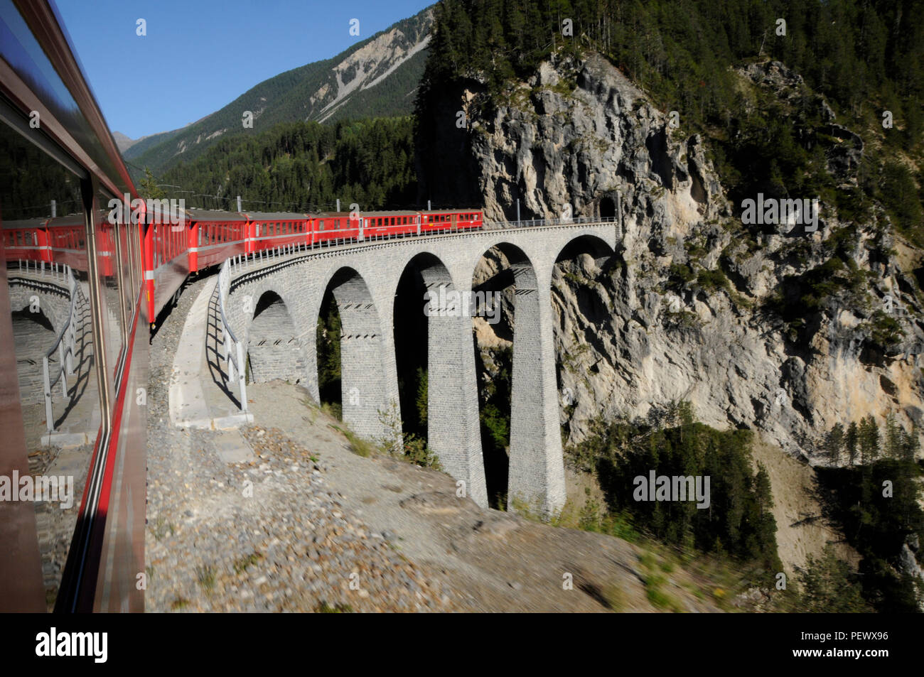 The Rhätische railway on its way through the Unesco World Heritage in the Swiss alps - Stock Image