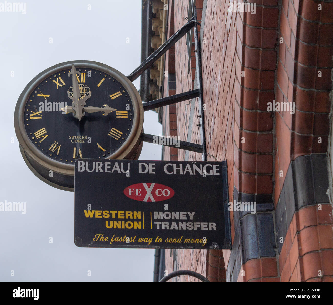 western union sign on a redbrick wall below a large clock face. - Stock Image