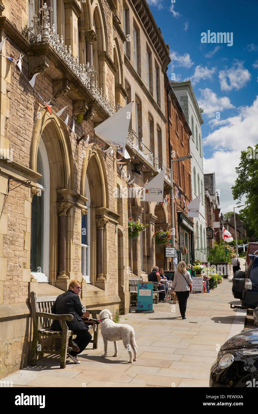 UK, Cumbria, Eden Valley, Appleby, Boroughgate, visitors sat outside in sunshine - Stock Image