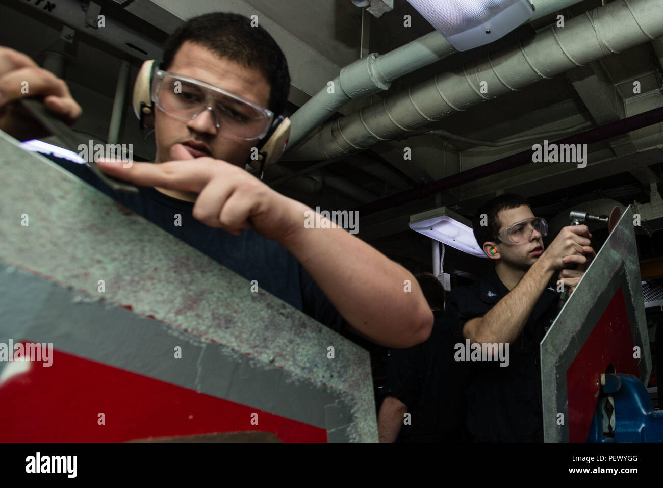 160211-N-MY174-009 PACIFIC OCEAN (Feb. 11, 2016) - Damage Controlman 3rd Class Felice Gabardi, from Boston, and Hull Maintenance Technician 3rd Class Anthony Hatcher, from Marsville, Calif., fabricate rat guards in USS John C. Stennis' (CVN 74) repair shop. Providing a combat-ready force to protect collective maritime interests, Stennis is operating as part of the Great Green Fleet on a regularly scheduled Western Pacific deployment. (U.S. Navy photo by Mass Communication Specialist Seaman Tomas Compian / Released) - Stock Image