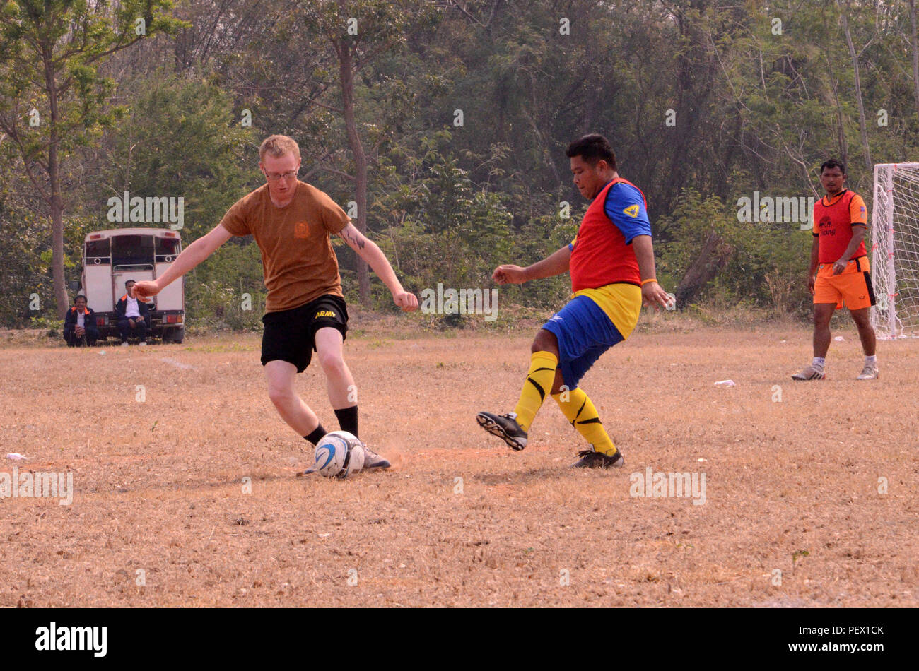 U.S. Army Pfc. Davie Cook, a carpenter and mason with 643rd Engineering Company out of Schofield Barracks, Hawaii goes for the ball during a soccer match between civilians, U.S., Indian, and Thai Soldiers, Feb. 11, 2016, at the 14th County Friendship Sport at Lamsonthi District. The match was played at Pa Mai Sublungka School's soccer field and included merriment and several games to include soccer, tug-of- war and relay races. This year the U.S. soldiers joined the festivities, by taking a break from constructing a multipurpose building at Banradbumrung School. The multipurpose building is on - Stock Image