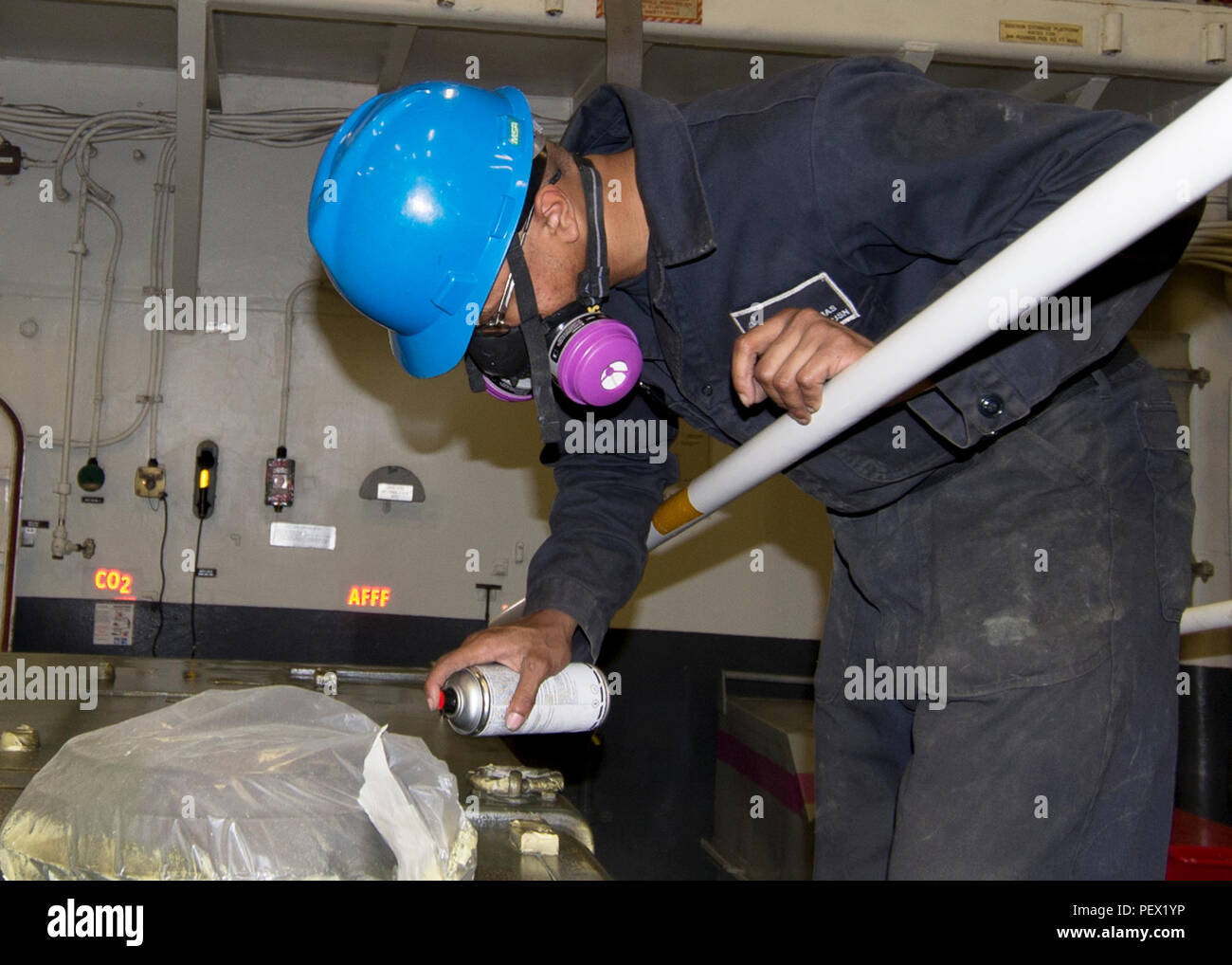160213-N-GV721-022 PACIFIC OCEAN (Feb. 13, 2016) Aviation Support Equipment Technician Seaman Malik Thomas paints a V-22 portable hydraulic power supply (PHPS) in the hanger bay of USS Boxer (LHD 4). More than 4,500 Sailors and Marines from Boxer Amphibious Ready Group and embarked 13th Marine Expeditionary Unit (13th MEU) are transiting the Pacific Ocean en route to the U.S. 5th and 7th Fleet areas of operations. (U.S. Navy photo by Mass Communication Specialist 2nd Brian Caracci/Released) - Stock Image