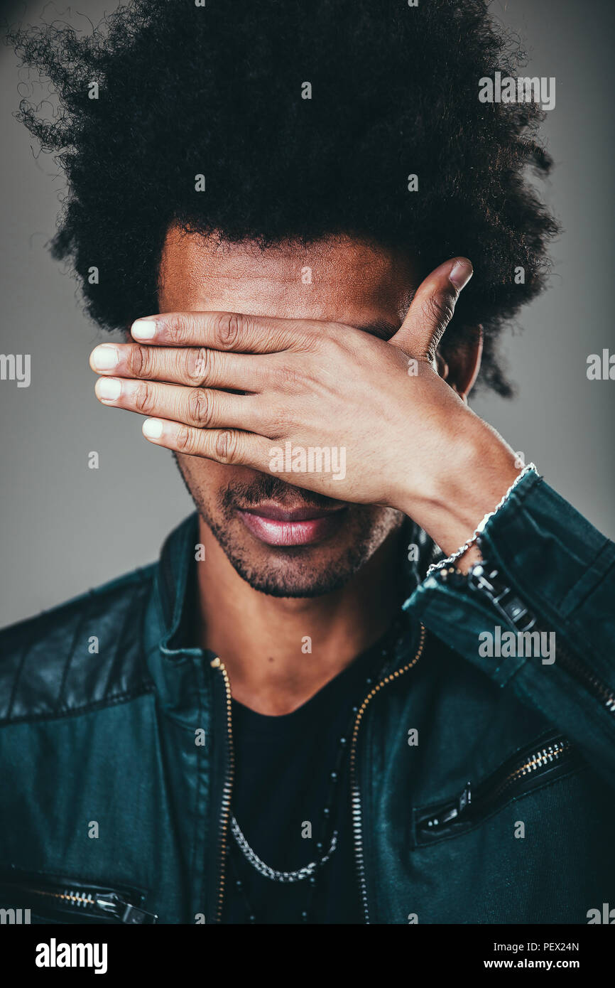 Unrecognizable unshaven African American man with tousled hair making facepalm gesture, covering eyes while feeling ashamed, standing against blank st - Stock Image