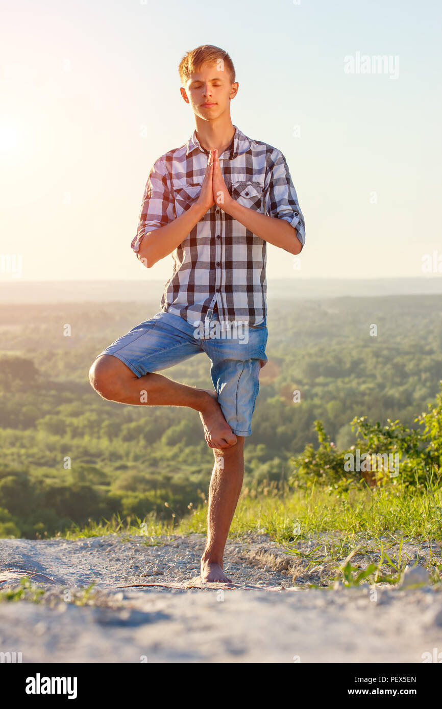 young man doing yoga outdoors in the sun health concept - Stock Image