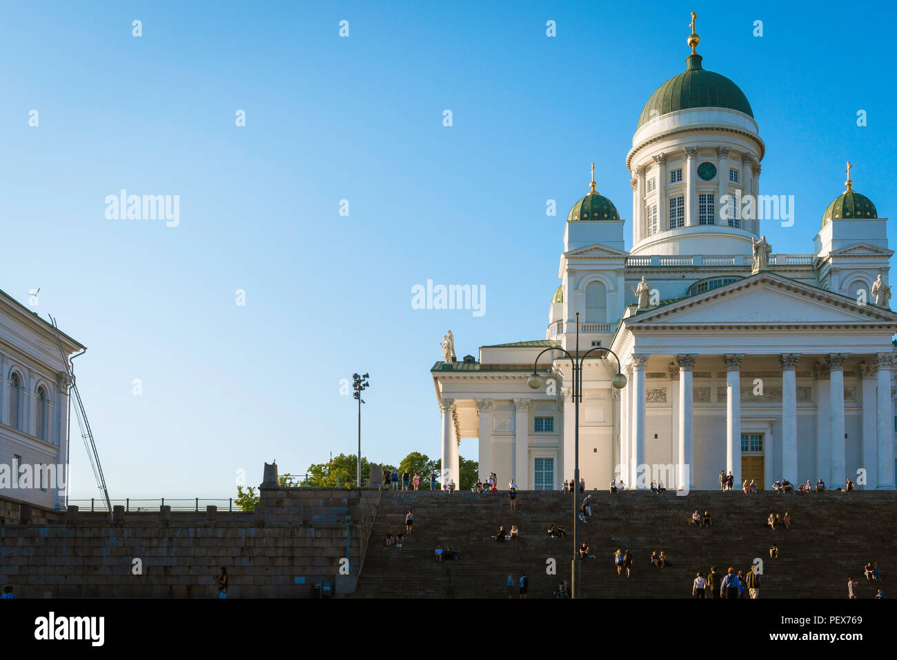 Finland tourism summer, view at sunset of the Lutheran Cathedral in Helsinki with tourists sitting on or ascending the grand staircase to its entrance. - Stock Image