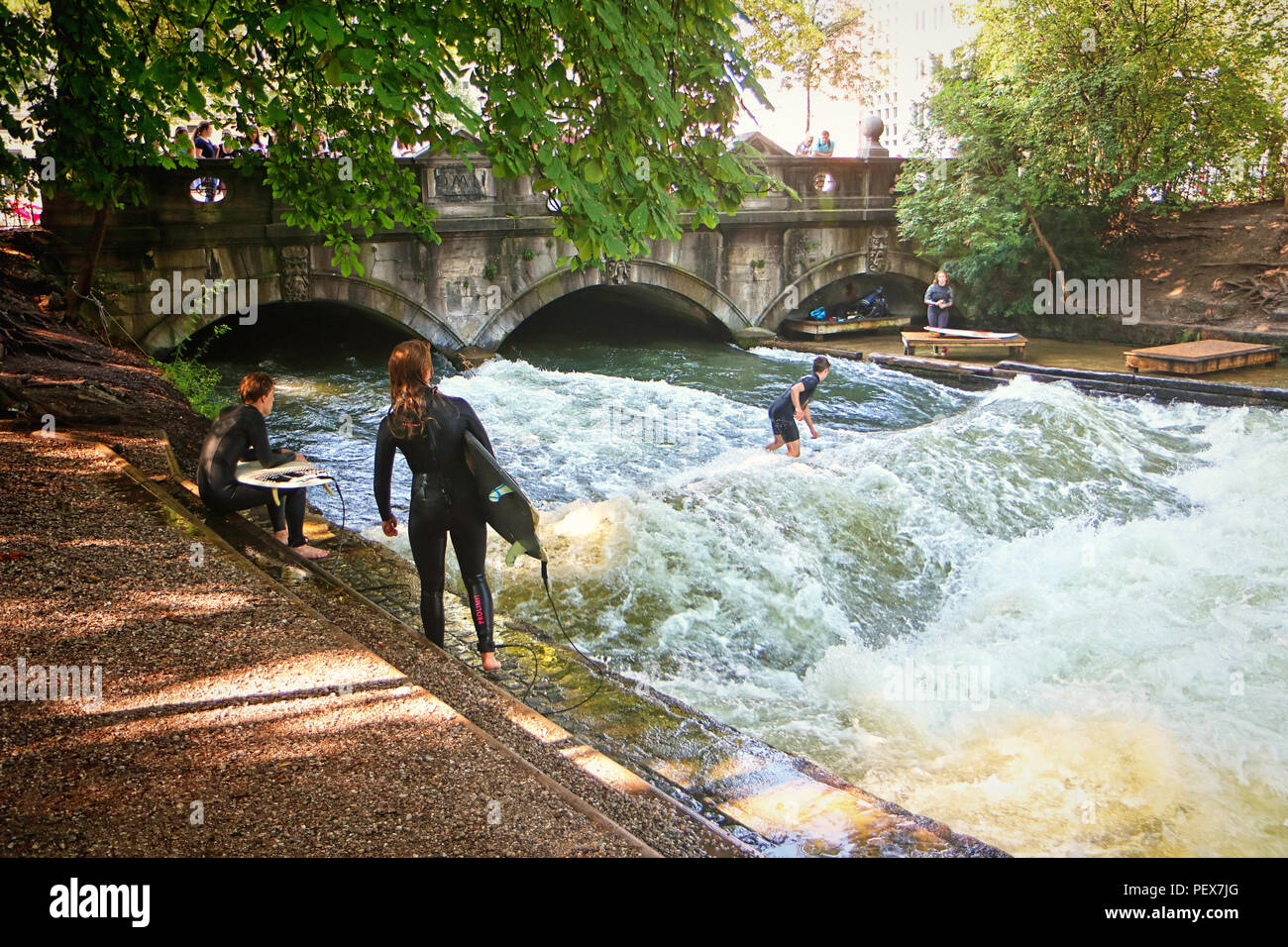 MUNICH, GERMANY - JULY 24, 2018 -  Munich, surfers in diving  suit practice on the artificial wave on the Eisbach, small river across the Englischer G - Stock Image